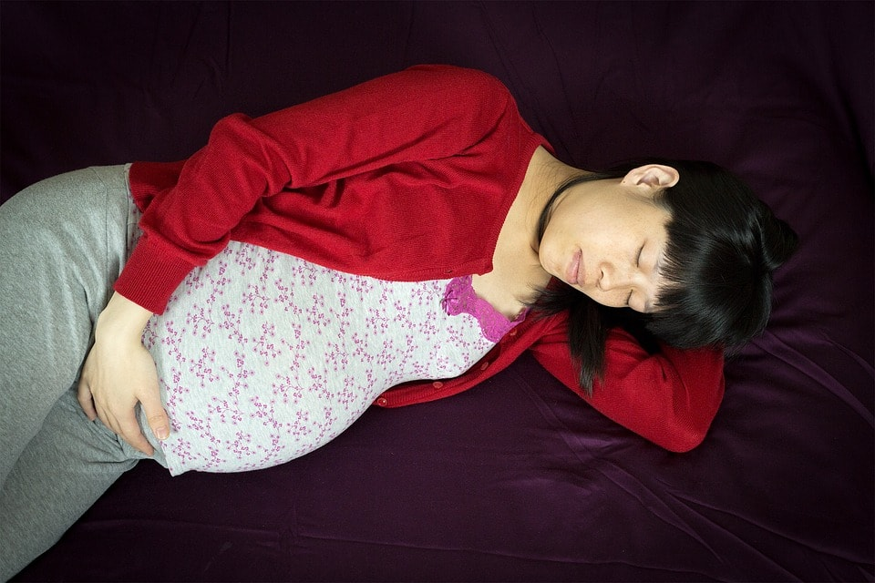 A Pregnant Women Wearing Red Shirt and Sleeping on Her Bed